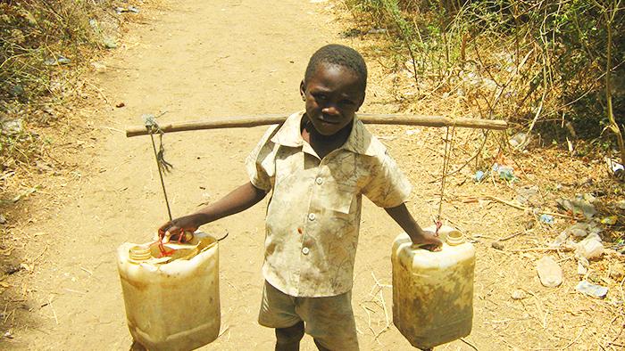 niño cargando agua